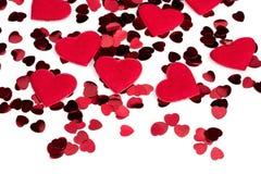 Confettis de coeurs et coeur rouges de tissu sur le fond blanc Photos stock