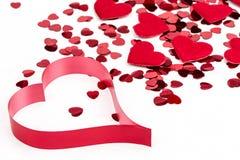 Confettis de coeurs et coeur rouges de tissu sur le fond blanc Photo stock