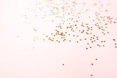 Confettis de couleur d'or sur le rose photographie stock