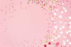 Confettis de f?te assortis de scintillement d'or sur le rose photos stock