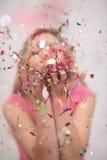 Confettis de soufflement de femme dans le ciel Image stock