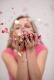 Confettis de soufflement de femme dans le ciel Photo stock