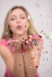 Confettis de soufflement de femme dans le ciel Photos stock