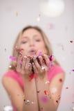 Confettis de soufflement de femme dans le ciel Photographie stock libre de droits