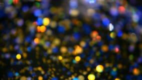 Confettis multicolores miroitants Defocused de scintillement, fond noir Taches lumineuses de bokeh de fête abstrait de vacances clips vidéos