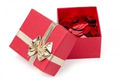 Confettis rouges de coeurs dans la boîte sur le fond blanc Photo stock