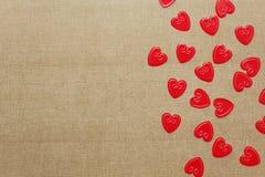 Confettis rouges de coeurs sur le fond beige Photo libre de droits