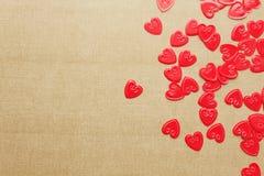 Confettis rouges de coeurs sur le fond beige Photos libres de droits