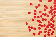 Confettis rouges de coeurs sur le fond en bois Image stock