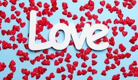Confettis rouges sur le fond bleu avec amour Images libres de droits