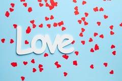 Confettis rouges sur le fond bleu avec amour Photo stock