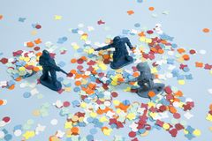 Confettis soldiers. Battle between three plastic soldiers on a blue pop vibrant background with confettis. Minimal color still life photography Royalty Free Stock Photography