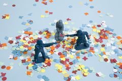 Confettis soldiers. Battle between three plastic soldiers on a blue pop vibrant background with confettis. Minimal color still life photography Stock Images
