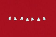 Confettis sous la forme d'arbre de Noël sur un rouge Images stock