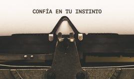 Confia en tu instinto, Spanish text for Trust Your Instinct. Confia en tu instinto, Spanish text for Trust Your Instinct, on paper in vintage type writer Stock Image