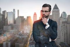 Confiado en su estilo Hombre de negocios barbudo hermoso que toca su barbilla y que mira lejos mientras que se coloca al aire lib imagen de archivo libre de regalías
