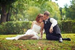 Confiance et étreinte - le couple de mariage se repose au sol vert Image libre de droits