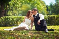 Confiance et baiser - les jeunes mariés s'asseyent sur l'herbe en parc Image stock