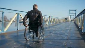 Confianza en sí mismo discapacitada, inválido masculino en la silla de rueda, gente y almacen de video