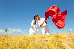 Confidence. Playful confident couple of mid adult man and woman standing in yellow corn field together embracing in casual clothes and throwing a red big scarf royalty free stock photo