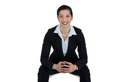 Confidence businesswoman sitting against white background. Portrait of confidence businesswoman sitting against white background royalty free stock photo