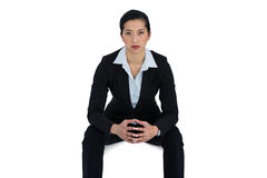 Confidence businesswoman sitting against white background. Portrait of confidence businesswoman sitting against white background stock photography