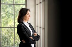Confidence Caucasian businesswoman crossed her arms and  looking out the window. Portrait of confidence Caucasian businesswoman crossed her arms and  looking out Royalty Free Stock Photos