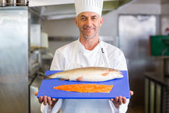 Confidence chef holding tray of raw fish in kitchen Royalty Free Stock Photo