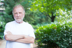 Confidence. Closeup portrait of happy, confident, cheerful, smiling senior mature man, arms folded crossed, isolated outside outdoors green trees foliage Stock Photography