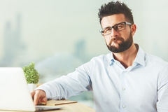 Confidence concept. Handsome caucasian man with approving expression using laptop. Confidence concept stock image
