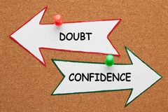 Confidence Doubt Concept. Confidence vs Doubt words on paper arrow pinned on cork board. Business concept royalty free stock photo