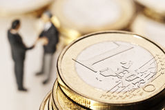 Confidence in the euro currency. One euro coin in the foreground, in the background two businessmen shaking hands Stock Photography