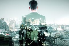 Confidence and lifestyle concept. Back view of young businessman on abstract city background. Confidence and lifestyle concept. Double exposure stock photo