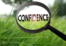 Confidence. Magnifying glass with the word confidence on grass background. Selective focus royalty free stock image