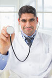 Confidence male doctor holding stethoscope Royalty Free Stock Images
