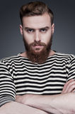 Confidence and masculinity. Confident young bearded man in striped clothing keeping arms crossed and looking at camera while standing against grey background Royalty Free Stock Photo