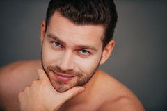 Confidence and masculinity. Confident young shirtless man looking at camera and smiling while holding hand on chin and sitting against grey background Royalty Free Stock Photography