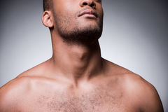 Confidence and masculinity. Cropped image of young shirtless African man standing against grey background Royalty Free Stock Photography
