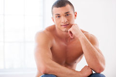 Confidence and masculinity. Handsome young muscular man holding hand on chin and smiling Stock Photo
