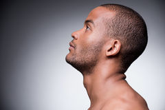 Confidence and masculinity. Side view of young shirtless African man looking up while standing against grey background Stock Images