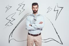 Confidence and power. Charming bearded man wearing a drawn cape with crossed arms is looking at camera while standing