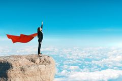 Confidence and risk concept. Side view of super hero woman with cape standing on cliff. Bright sky background. Confidence and risk concept stock images