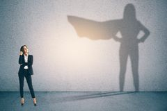 Confidence and success concept. Attractive businesswoman with superhero shadow on concrete wall background. Confidence and success concept stock photos