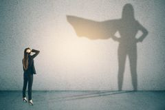 Confidence and success concept. Thoughtful businesswoman with superhero shadow on concrete wall background. Confidence and success concept royalty free stock photography