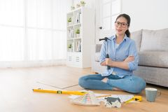 Confidence successful female interior engineer. Holding hammer tool sitting on wooden floor design new working house case and face to camera smiling Royalty Free Stock Photos