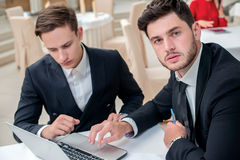 Confidence in the work. Two successful and confident businessman. Sitting at the table in a business office in full costume in the office and working at a Royalty Free Stock Photo