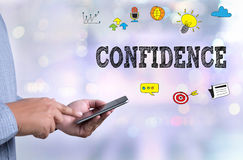 CONFIDENCE   YES I CAN. Person holding a smartphone on blurred cityscape background Royalty Free Stock Photography