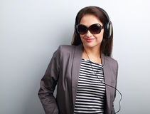 Confidence young woman in sunglasses listening the music in head. Phones and looking happy on blue background royalty free stock photography