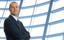 Confident. Business man with his arms crossed with windows royalty free stock photo