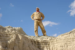 Confident Active Senior Man. Confident senior man standing proudly high up on a cliff he climbed. To view all four images from this series keyword: khaki/man Royalty Free Stock Photo